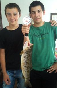 Dos jóvenes pescadores nos muestran su captura de una trucha de más de dos kilos